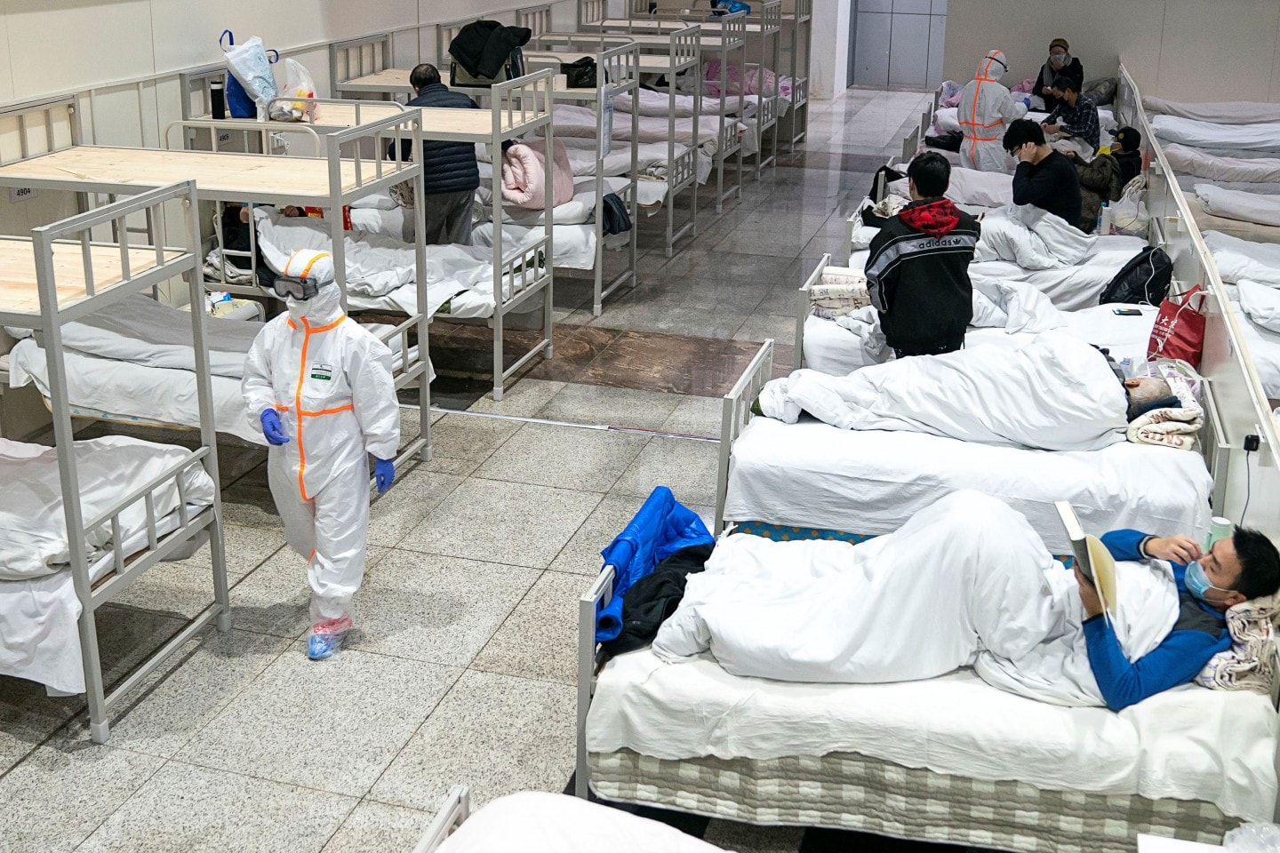 Medical workers in protective suits attend to patients at the Wuhan International Conference and Exhibition Center, which has been converted into a makeshift hospital, in Wuhan, China, on Feb. 5. (China Daily/Reuters)